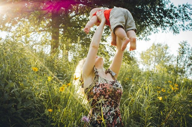 Woman carrying her baby in the grass, on a sunny day in suburbs of Washington DC