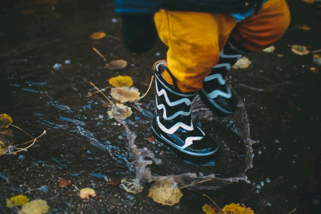 a toddler running in rubber boots