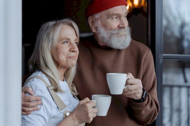An elderly couple drinking coffee.